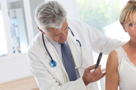 Anziana donna medico di consulenza per il controllo della pelle