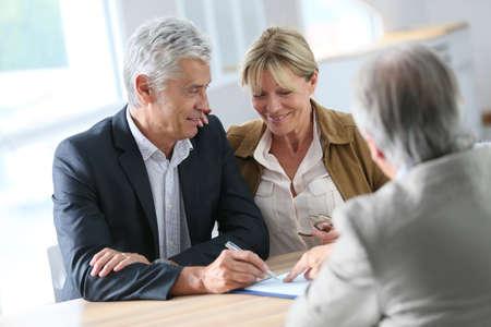 Réunion senior couple agent immobilier pour l'investissement