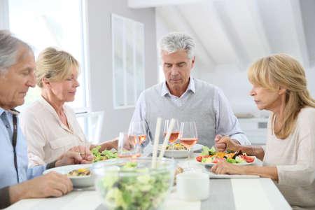 personas comiendo: Grupo de personas dando bendiciones antes de comer