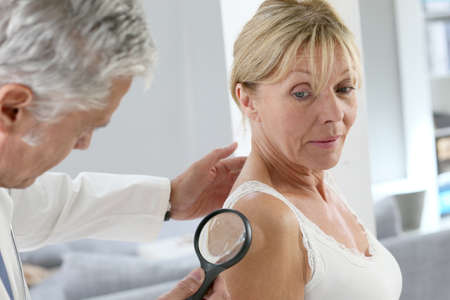 dermatologist: Elderly woman consulting doctor for skin control