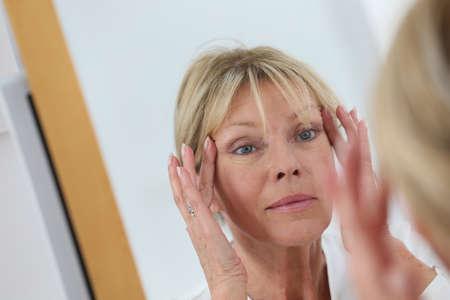 Senior femme regardant dans le miroir sa peau