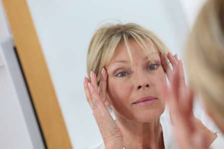 aging face: Senior woman looking at her skin in mirror