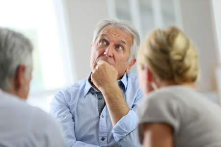 retirement community: Senior man attending meeting with group therapist