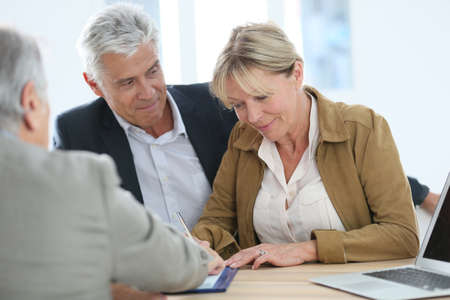 old sign: Senior couple meeting real-estate agent for investment