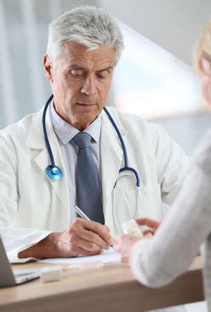 persona enferma: Doctor que tiene consulta con el paciente en el consultorio Foto de archivo