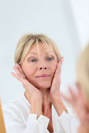 woman in the mirror: Senior woman looking at her skin in mirror
