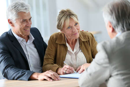 real estate sign: Senior couple meeting real-estate agent for investment