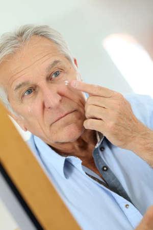 antiaging: Senior man applying anti-aging lotion on his face