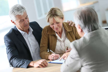 buying a house: Senior couple meeting real-estate agent for investment