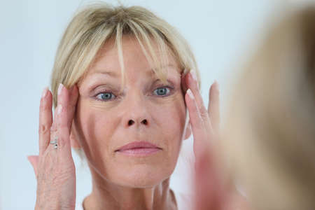 年配の女性が鏡の中の彼女の肌を見て