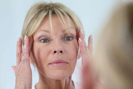 Hogere vrouw die haar huid in de spiegel