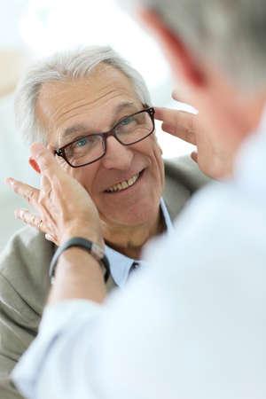 persona mayor: Hombre mayor que probar nuevas gafas de, tienda de óptica
