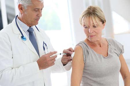 vacunacion: Doctor que inyecta la vacuna contra la gripe en el brazo del paciente Foto de archivo