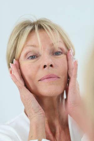 mirror?: Mujer mayor que mira la piel en espejo