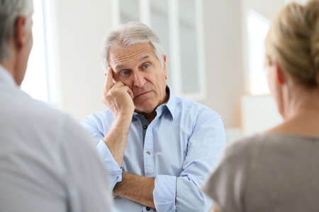 attending: Senior man attending meeting with group therapist
