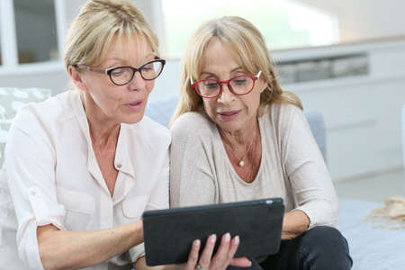 adult woman: Senior women at home using digital tablet