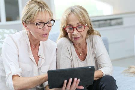 senior women: Senior women at home using digital tablet