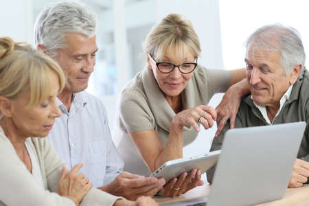 computer clubs: Group of retired senior people using laptop and tablet