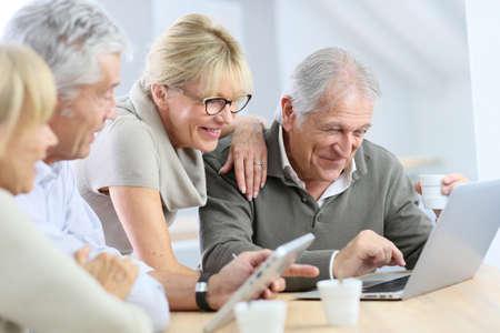 jubilados: Grupo de gente mayor jubilados usan la computadora portátil y la tableta