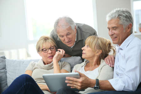 senior men: Group of retired people sitting in sofa and using tablet