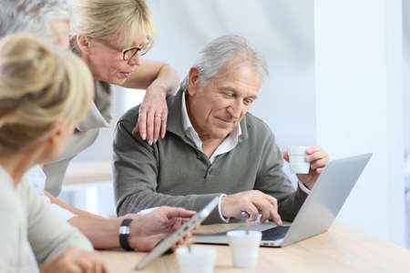 old desk: Group of retired senior people using laptop and tablet