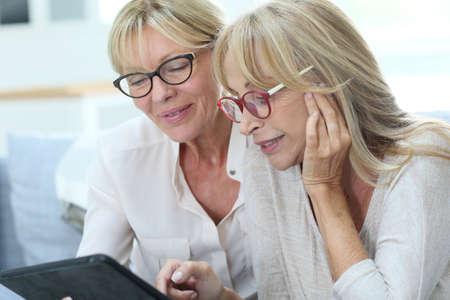 senior friends: Senior women at home using digital tablet