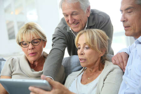 retirement: Group of retired people sitting in sofa and using tablet