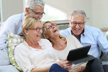 デジタル タブレットを使用して眼鏡の年長の友人のグループ 写真素材