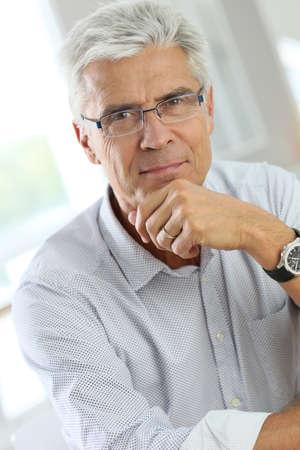 specs: Portrait of senior man with grey hair wearing eyeglasses