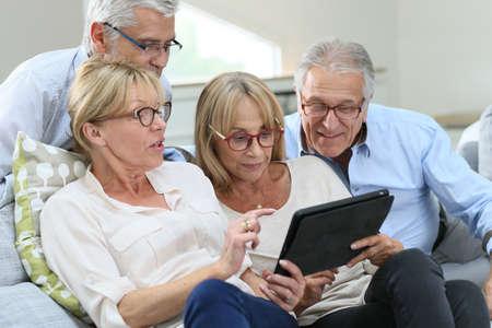 senior group: Group of senior friends with eyeglasses using digital tablet