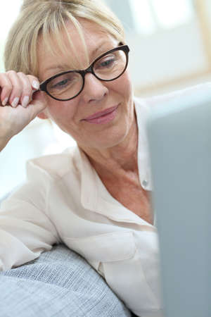 old sofa: Senior woman with eyeglasses connected on digital tablet Stock Photo