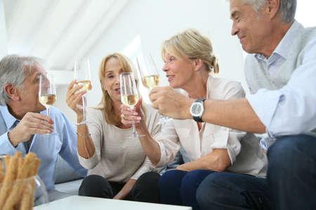 gente celebrando: Grupo de gente mayor celebran con champ�n Foto de archivo