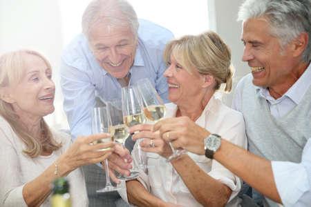 Gruppo di gente maggiore festeggiare con champagne