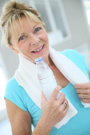 tomando agua: Retrato de la mujer mayor en sala de fitness de agua potable