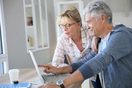 Senior couple à la maison frais de contrôle sur Internet