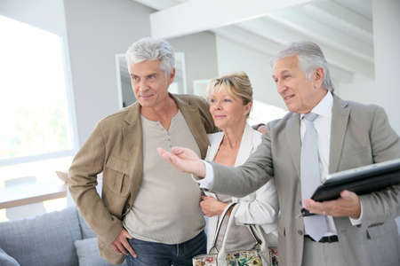 realestate: Senior couple with real-estate agent visiting house for sale