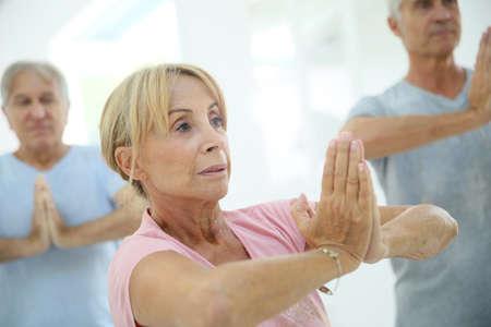 senior yoga: Group of senior people doing fitness exercises in gym