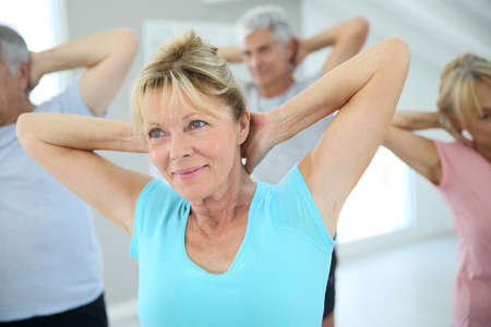 estiramiento: Gente mayor que se extiende en el gimnasio