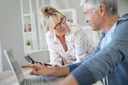 home expenses: Senior couple at home checking expenses on internet