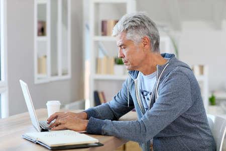 trabajando en casa: Hombre mayor que trabaja desde su casa en el ordenador portátil