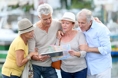 senior group: Senior tourists using tablet on visiting journey