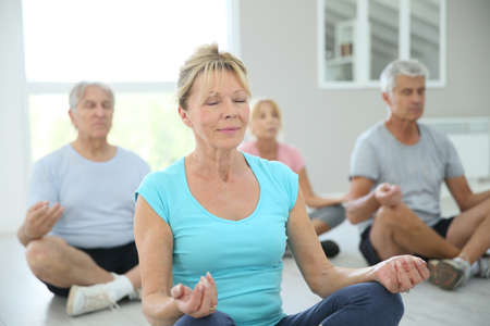 tercera edad: Grupo de gente mayor que hace ejercicios de yoga Foto de archivo