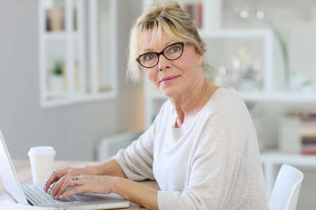 homeoffice: Portrait of senior woman working on laptop computer