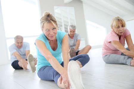 estiramientos: Grupo de gente mayor que hace ejercicios de estiramiento Foto de archivo