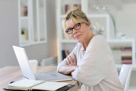 homeoffice: Portrait of senior woman working on laptop computer