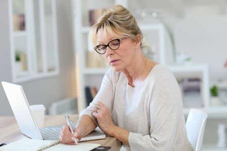 Portret van senior vrouw die werkt op een laptop computer