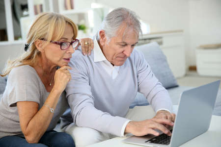 websurfing: Senior couple at home websurfing on laptop computer