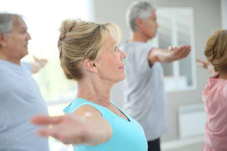 tercera edad: Gente mayor que se extiende en el gimnasio