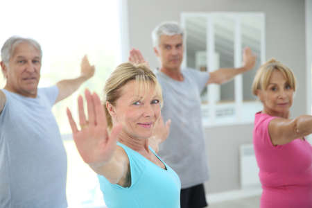 Senior people stretching out in fitness room