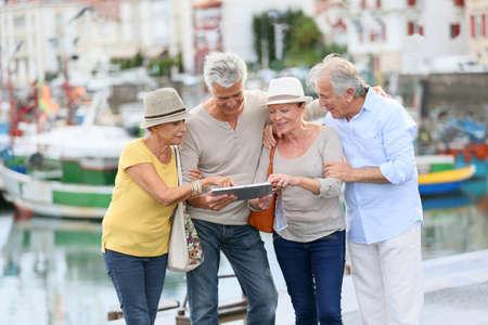 viagem: Casais idosos que olham o mapa em viajar viagem Banco de Imagens